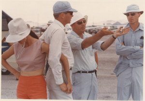 George and Suzanne Moffat, holding hands, on tarmac discusses the day's competition with other glider pilots.
